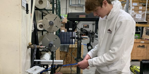 STEM Senior Kyle Paris demonstrates the 3D-printed device he created to speed up production at Panther Industries
